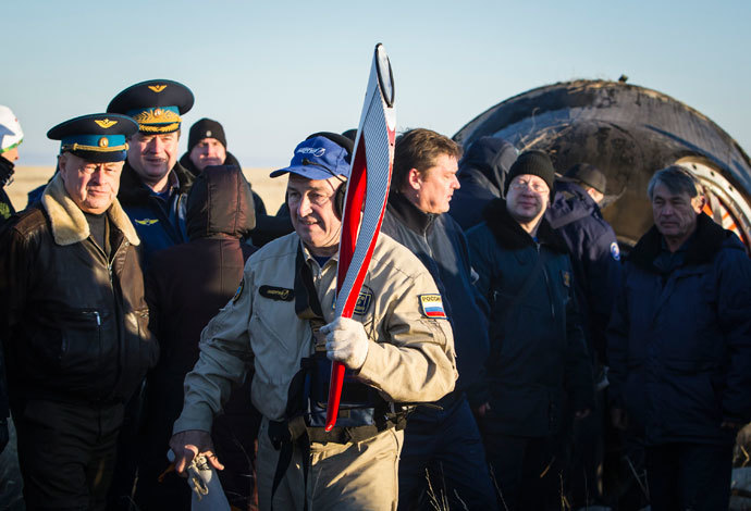 A member of ground personnel carries the torch of the 2014 Sochi Winter Olympic Games delivered from orbit in the Soyuz TMA-09M capsule after its landing in a remote area near the town of Zhezkazgan in central Kazakhstan November 11, 2013. (Reuters / Shamil Zhumatov)