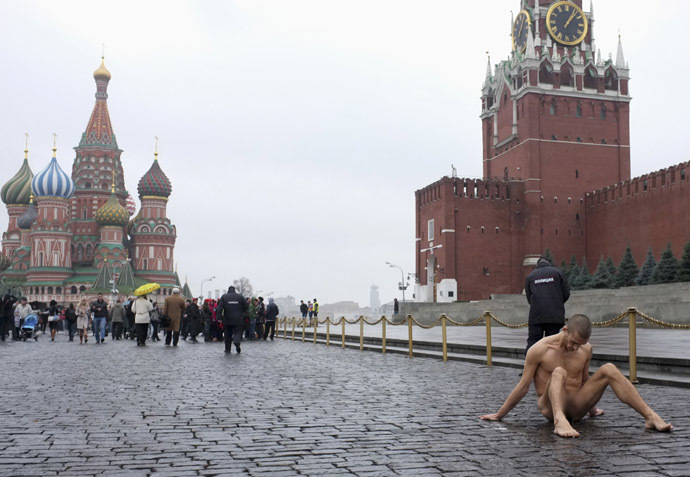 Artist Pyotr Pavlensky sits on the pavestones of Red Square during a protest action in front of the Kremlin wall in central Moscow, November 10, 2013. (Reuters/Maxim Zmeyev)