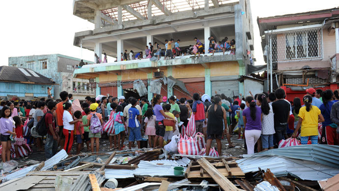 Residents watch as others throw looted goods from a warehouse in the town of Guiuan, Eastern Samar province in the central Philippines on November 11, 2013.(Reuters / Ted Aljibe)