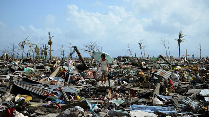 A surivor walks among the debris of houses destroyed by Super Typhoon Haiyan in Tacloban in the eastern Philippine island of Leyte on November 11, 2013.(AFP Photo / Noel Celis)