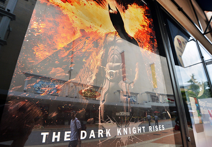 "People walk past a poster of the new Batman movie ""The Dark Knight Rises"" outside a theater in Silver Spring, Maryland (AFP Photo / Jewel Samad)"