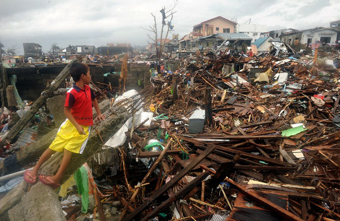 A boy looks at the debris of destroyed houses in Tacloban, on the eastern island of Leyte on November 12, 2013, after Super Typhoon Haiyan, the most powerful storm in the world this year, hit the Philippines on November 8. (AFP Photo / Noel Celis)