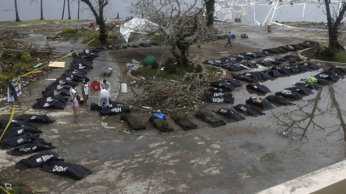 Survivors stand near bags containing bodies of typhoon victims in Tacloban city, which was devastated by Typhoon Haiyan, in central Philippines November 12, 2013. (Reuters / Romeo Ranoco)