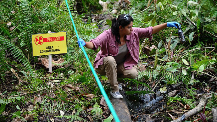 A woman shows crude oil from the Aguarico 4 well near Aguarico, Sucumbios province, Amazonian Peru, on September 17, 2013. (AFP Photo / Rodrigo Buendia)
