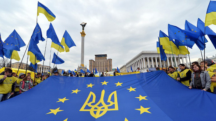"""Activists of Ukrainian movement """"For European Future"""" hold EU flag with the Ukraine national emblem during their rally at Independence  Square in Kiev on October 30, 2013. (AFP Photo / Sergei Supinski)"""