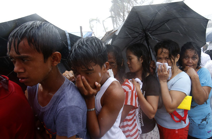 Victims queue for food and water during a heavy downpour in the aftermath of super typhoon Haiyan in Tacloban city, central Philippines - November 14, 2013. (Reuters)