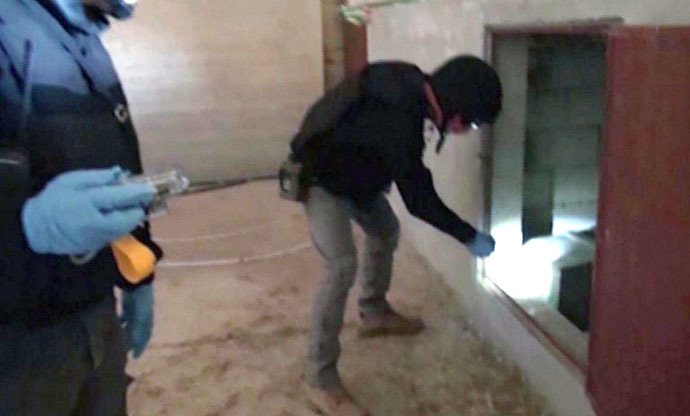 An image grab taken from Syrian television on October 10, 2013 shows inspectors from the Organisation for the Prohibition of Chemical Weapons (OPCW) at work at an undisclosed location in Syria. (AFP Photo)