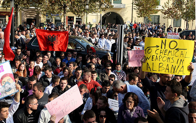 Albanian environmental activists hold up national flags and signs as they take part in a protest in front of the Albanian parliament in Tirana on November 14, 2013, over the possibility of the Republic of Albania processing and destroying 1.000 tons of chemical weapons from Syria in its military facilities. (AFP Photo)