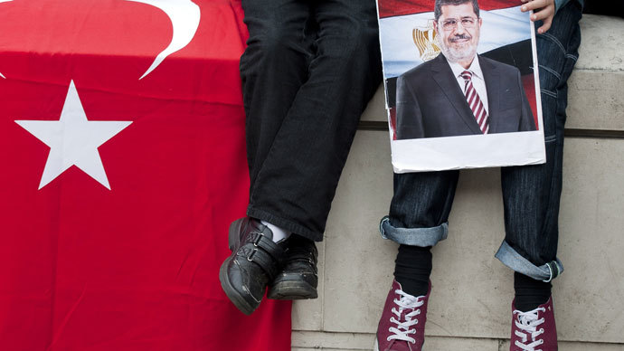 A young demonstrator holds a picture of ousted Egyptian president Mohamed Morsi during a protest in support of the Muslim Brotherhood outside 10 Downing Street in central London on August 18, 2013.(AFP Photo / Will Oliver)