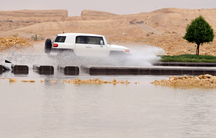 A car drives through a flooded street in northern Riyadh, on November 17, 2013, after heavy rains fell overnight in the Saudi capital, caused floods and traffic jams which forced the Saudi Eduction Ministry to suspend studies in schools and universities for one day (AFP Photo / Fayez Nureldine)