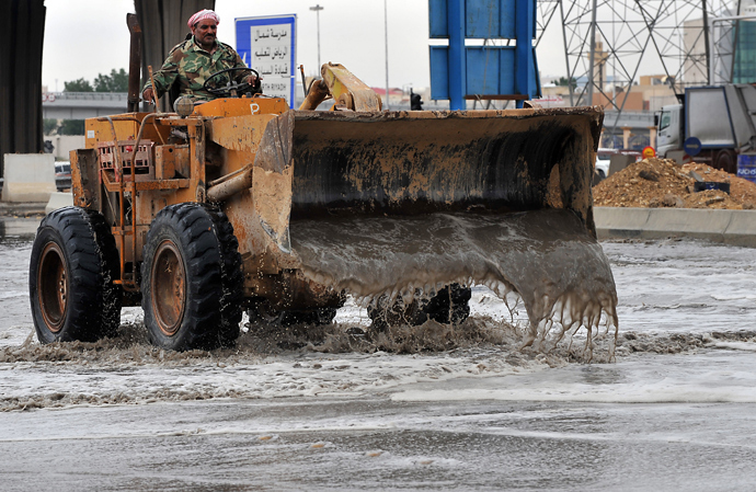 A Saudi labourer tries to clear a flooded street in northern Riyadh, on November 17, 2013, after heavy rains fell overnight in the Saudi capital, causing floods and traffic jams and forcing the Saudi Eduction Ministry to suspend studies in schools and universities for one day (AFP Photo / Fayez Nureldine)