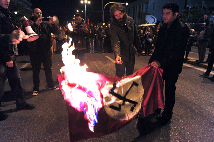 Leftist students burn a Nazi flag in front of the US embassy in Athens, during a march commemorating the 1973 students uprising against the military junta. Tens of thousands marched in Greece on November 17 (AFP Photo / Louisa Gouliamaki)