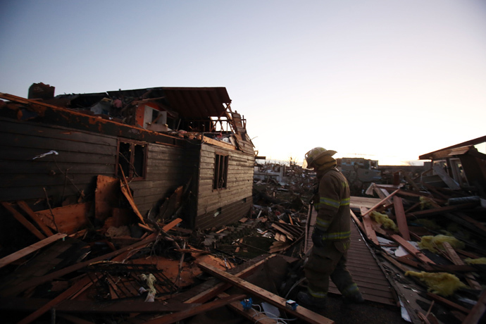 A firefighter searches through debris after a tornado struck on November 17, 2013 in Washington, Illinois. (Tasos Katopodis / Getty Images / AFP)