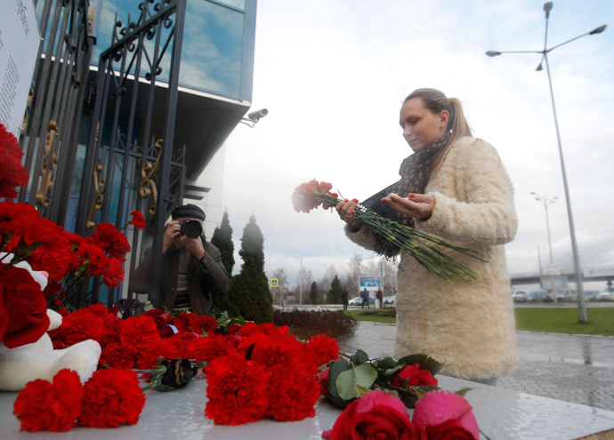 A woman lays flowers near a fence of Kazan airport, where a Tatarstan Airlines Boeing 737 crashed, November 18, 2013 (Reuters / Maxim Shemetov)