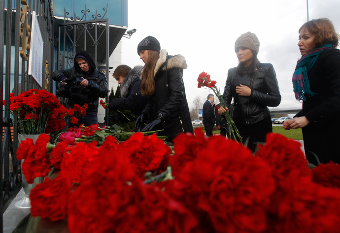 People lay flowers near a fence of Kazan airport, where a Tatarstan Airlines Boeing 737 crashed, November 18, 2013 (Reuters / Maxim Shemetov)