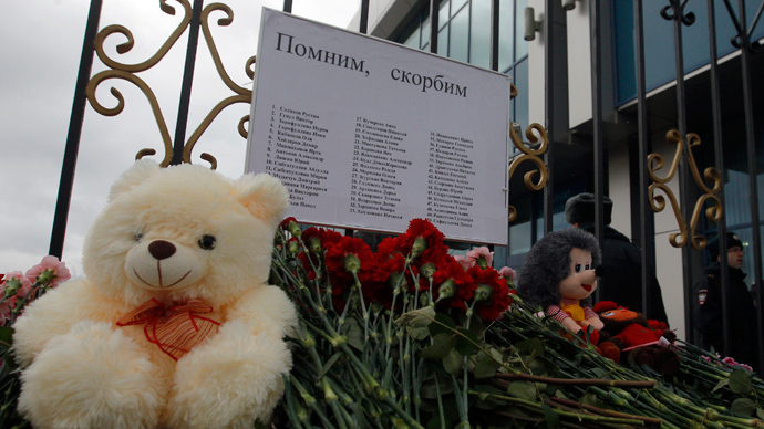 Flowers and stuffed toys, part of a makeshift memorial, are seen left near a fence of Kazan airport, under a sign giving the names of the victims of a Tatarstan Airlines Boeing 737 crash, November 18, 2013 (Reuters / Maxim Shemetov)