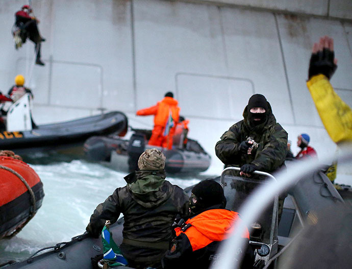 A handout photo taken by Greenpeace on September 18, 2013, shows a camouflage clad mask wearing officer of Russian Coast Guard (2nd R) pointing a gun at a Greenpeace International activist (partly seen R) during an environmentalists' attempt to climb Gazprom's 'Prirazlomnaya' Arctic oil platform somewhere off Russia north-eastern coast in the Pechora Sea. (AFP Photo / Greenpeace / Denis Sinyakov)