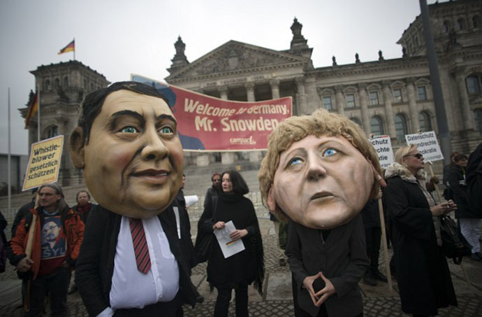 Campact activists wear masks of German Chancellor Angela Merkel (R) and the social democratic SPD party's leader Sigmar Gabriel and hold up a portrait of US whistleblower Edward Snowden in front of the Reichstag building housing the Bundestag (lower house of parliament) in Berlin on November 18, 2013. (AFP Photo / Johannes Eisele)