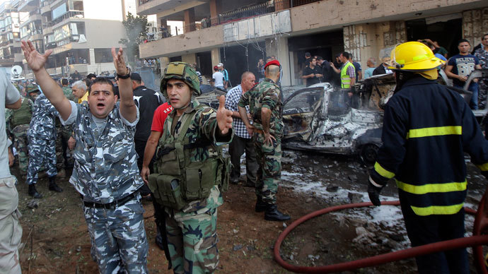 A soldier (in green, 2nd L) and policeman gesture at the site of the explosions near the Iranian embassy in Beirut November 19, 2013.(Reuters / Mahmoud Kheir)