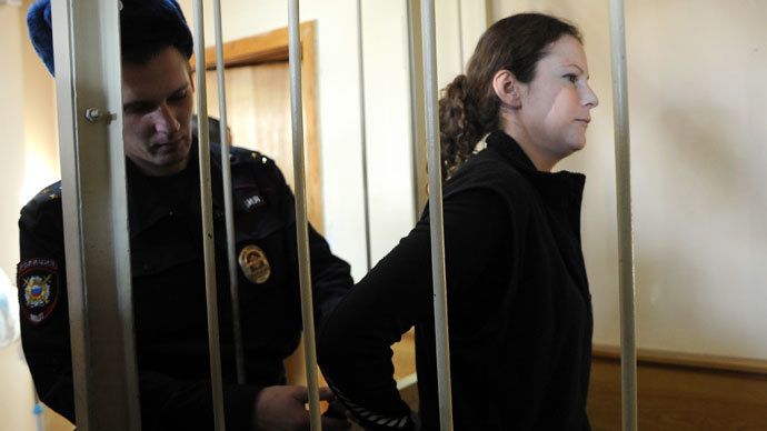 "A Russian police officer puts handcuffs on Greenpeace International activist, one of the ""Arctic 30,"" Ana Paula Alminhana Maciel from Brazil, in a defendant cage in a court in Russia's second city of Saint Petersburg, on November 18, 2013.(AFP Photo / Olga Maltseva)"