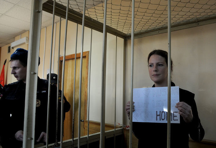 "Greenpeace International activist, one of the ""Arctic 30,"" Ana Paula Alminhana Maciel from Brazil, holds a poster as she stands in a defendant cage in a court in Russia's second city of Saint Petersburg, on November 18, 2013.(AFP Photo / Olga Maltseva)"