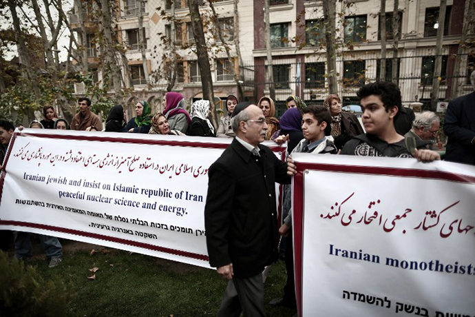 Iranian Jews hold banners as they attend a demonstration in front of the United Nation's building in Tehran on November 19, 2013 in support of Iran's nuclear program and Iranian negotiators on the eve of the new round of nuclear talks with world powers in Geneva. (AFP Photo / Behrouz Mehri)