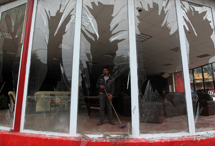 An Iraqi man clean debris from a shop after a car bomb attack in the Karrada neighborhood in central Baghdad on November 20, 2013. (AFP Photo/Ahmad Al-Rubaye)