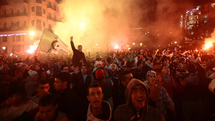 Fans of Algeria's soccer team hold the country's national flag as they celebrate in downtown Algiers, after their team defeated Burkina Faso in their 2014 World Cup qualifying second leg playoff soccer match, November 19, 2013. (Reuters/Ramzi Boudina)