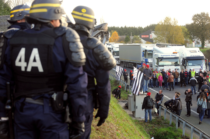 Anti-riot policemen (L) look at truck drivers blocking a part of a highway near Lanrodec, western of France, to protest against an environmental tax on November 16, 2013. (AFP Photo / Fred Tanneau)