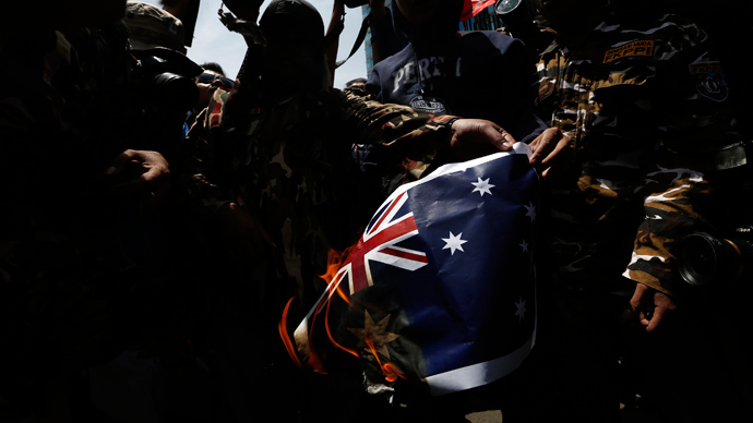 Protesters burn an Australian flag during a protest in front of the Australia embassy in Jakarta, November 21, 2013. (Reuters / Beawiharta)