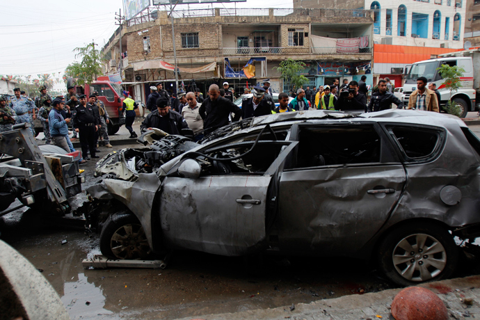 Residents gather at the site of a car bomb attack in Baghdad November 20, 2013. (Reuters / Ahmed Saad)
