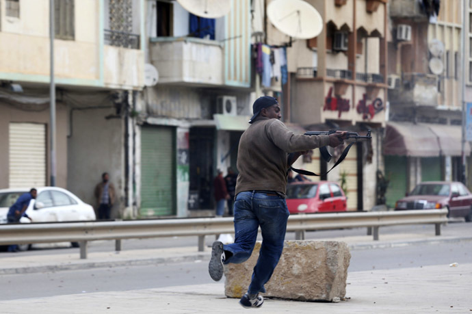 A resident, in support of the Libyan army, fires a weapon towards members of Islamist militant group Ansar al-Sharia during clashes between the group and a Libyan army special forces unit in the Ras Obeida area in Benghazi November 25, 2013. (Reuters/Esam Omran Al-Fetori)