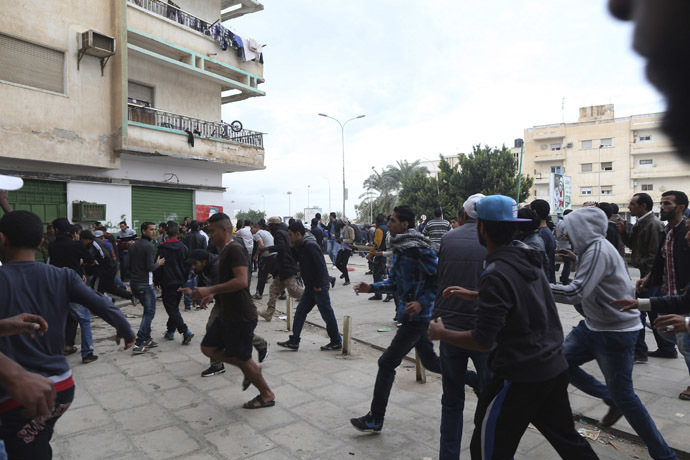 People flee from shooting during clashes between members of Islamist militant group Ansar al-Sharia and a Libyan army special forces unit in the Ras Obeida area in Benghazi November 25, 2013. (Reuters/Esam Omran Al-Fetori)