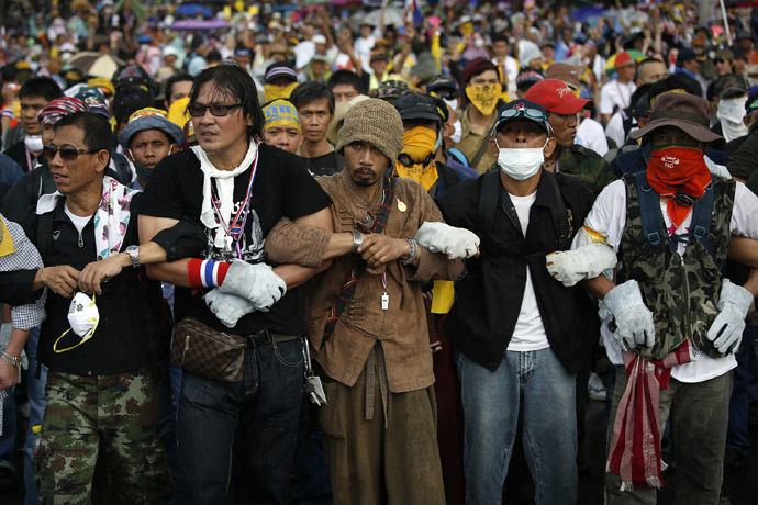 Anti-government protesters link their arms as they get ready to attack a police barricade near the Government house in Bangkok November 25, 2013. (Reuters/Damir Sagolj)