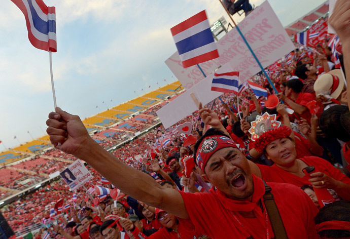 "Thai pro-government ""Red Shirts"" wave national flag as they gather at Rajamangala stadium in Bangkok on November 24, 2013. (AFP Photo)"