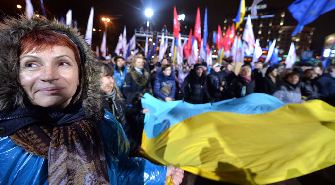 A woman together with other protesters waves an Ukrainian national flag during a rally of the opposition on European Square, on a second day of protests over the government's decision to scrap a key pact with the EU, in Kiev on November 25, 2013.(AFP Photo / Sergei Supinsky)