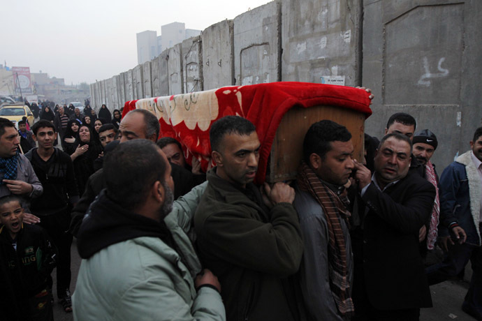 Mourners carry the coffin of a victim killed by a bomb attack in Baghdad's Sadriya district, November 26, 2013. (Reuters/Thaier Al-Sudani)