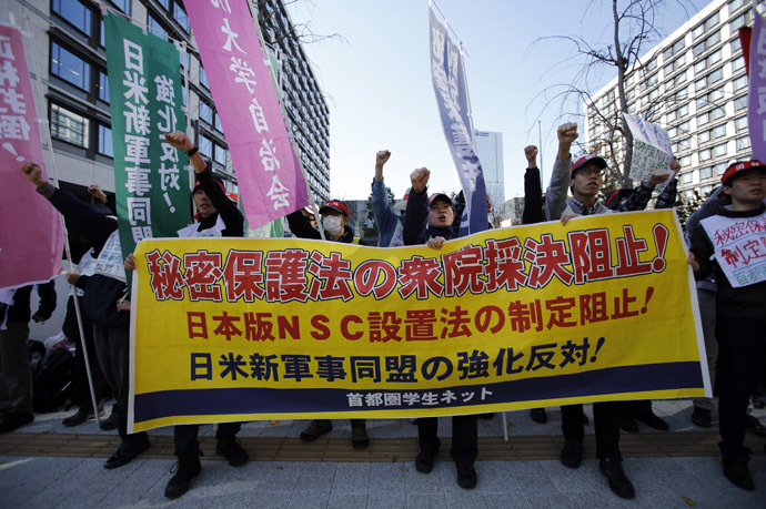 Protesters raise their fists as they shout slogans during a rally against the government's planned state secrets act in front of the parliament building in Tokyo November 26, 2013. (Reuters/Toru Hanai)