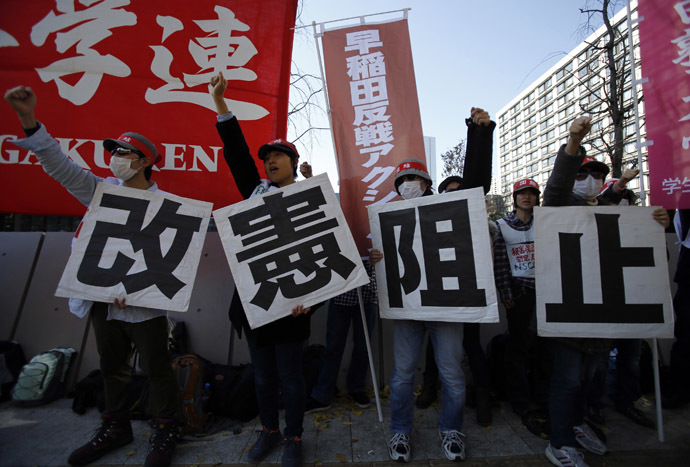 Protesters raise their fists as they shout slogans during a rally against the government's planned state secrets act in front of the parliament building in Tokyo November 26, 2013. (Reuters/Toru Hanai