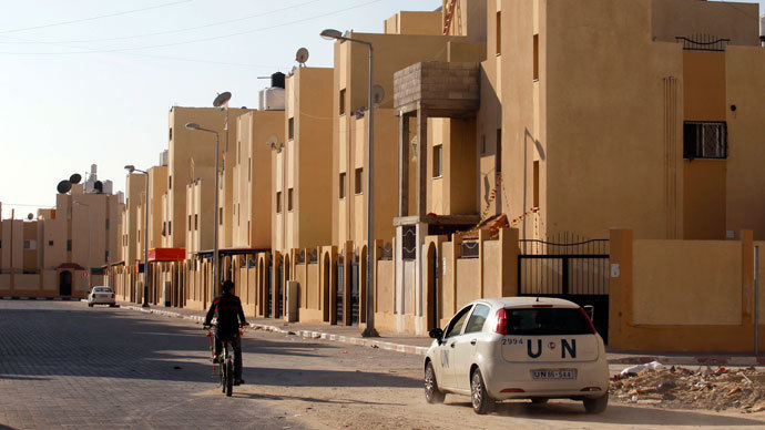 A United Nations (UN) car passes in front of new houses which are part of a project funded by the United Nations Relief and Works Agency for Palestine Refugees (UNRWA) in the southern Gaza Strip town of Rafah on November 21, 2013.(AFP Photo / Said Khatib)