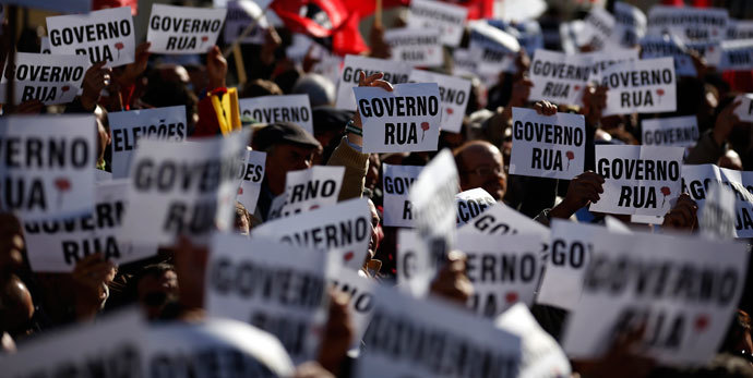 Members of CGTP-Intersindical workers union hold banners during a protest in front of Portuguese parliament in Lisbon November 26, 2013.(Reuters / Rafael Marchante)