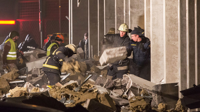 Firefighters clear the debris outside the Maxima shopping mall in Riga (RIA Novosti)