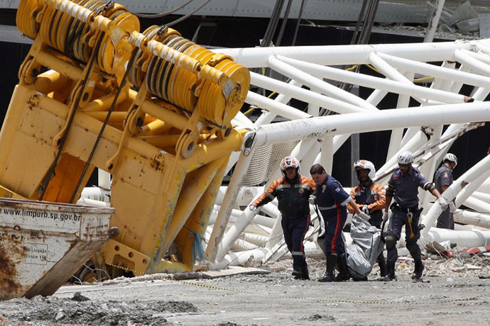 Rescuers carry the body of a worker who died after a crane fell across part of the metallic structure at the Arena de Sao Paulo --Itaquerao do Corinthians-- stadium, still under construction, on November 27, 2013 in Sao Paulo. (AFP Photo / Eduardo Viana)