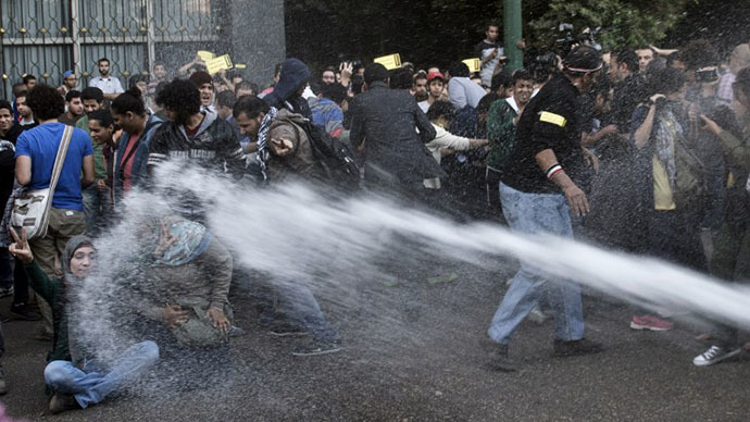 Egyptian policemen use a water canon to disperse protesters during a demonstration in downtown Cairo on November 26, 2013 against the new law passed the previous day regulating demonstrations. (AFP Photo / Khaled Desouki)