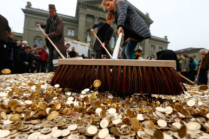 "Committee members use brooms to spread out five cent coins over the Federal Square during an event organised by the Committee for the initiative ""CHF 2,500 monthly for everyone"" (Grundeinkommen) in Bern October 4, 2013.(Reuters / Denis Balibouse)"