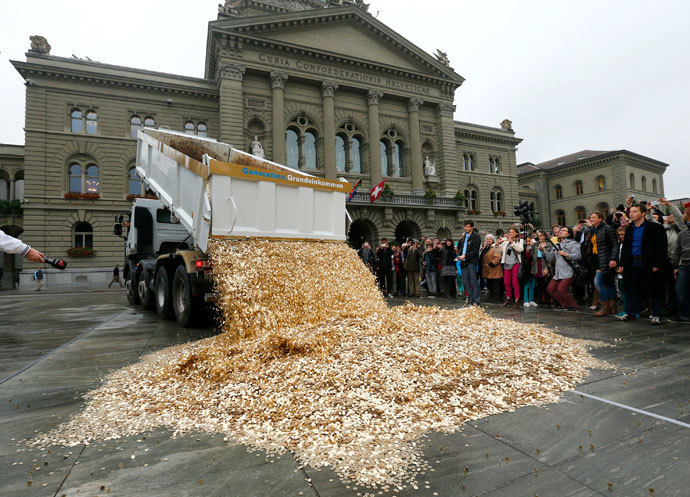 "A truck dumps five cent coins in the centre of the Federal Square during a an event organised by the Committee for the initiative ""CHF 2,500 monthly for everyone"" (Grundeinkommen) in Bern October 4, 2013. (Reuters / Denis Balibouse)"