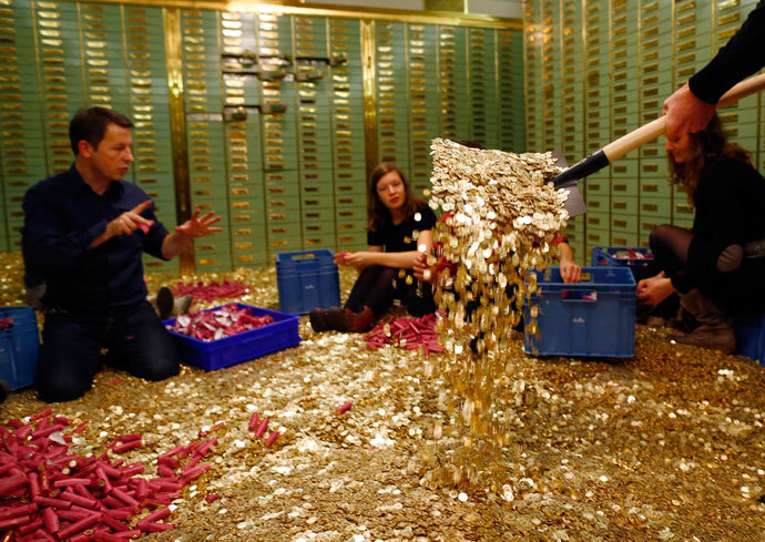 """Committee members for the initiative """"CHF 2,500 monthly for everyone"""" (Grundeinkommen) open rolls of five cent coins in the old vault of the former Schweizerische Volksbank in Basel October 1, 2013.(Reuters / Ruben Sprich)"""