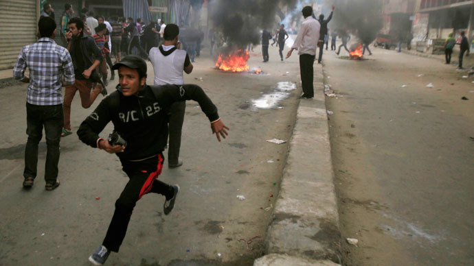 Supporters of the Muslim Brotherhood and ousted Egyptian President Mohamed Mursi flee and run near burning tyres, from tear gas fired by riot police and army, during clashes at El-Talbyia near Giza square, south of Cairo, November 29, 2013.(Reuters / Amr Abdallah Dalsh)