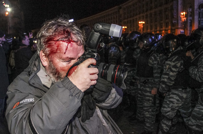 Wounded Reuters photographer Gleb Garanich, who was injured by riot police, takes pictures as riot police block protesters during a scuffle at a demonstration in support of EU integration at Independence Square in Kiev November 30, 2013. (Reuters)