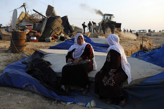 Bedouin women sit on rubble as Israeli policemen destroy the makeshift houses of the Al-Akarib bedouin village in the Israeli Negev desert on August 10, 2010 (AFP Photo/David Buimovitch)